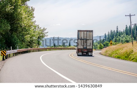 Big rig white day cab semi truck with roof spoiler transporting huge covered bulk semi trailer with ladder on the back wall moving on the turning winding road with yellow hills and green trees #1439630849