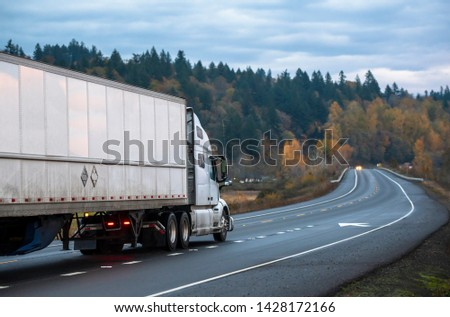 Big rig white long haul semi truck with semi trailer running with turned on headlights on rain dusted wet raining highway driving with another cars traffic in twilight evening time