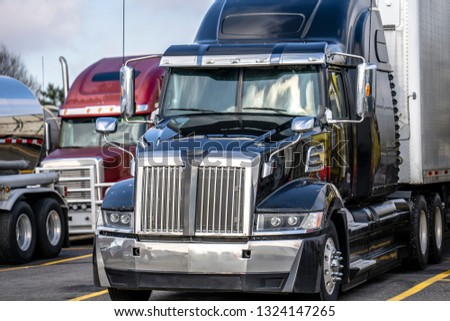 Big rigs commercial cargo haulers Semi Trucks with different semi trailers of various brands and models stand on truck stop parking for truck drivers rest and continue delivery routes as scheduled #1324147265