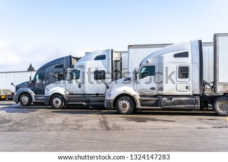 Big rigs commercial cargo haulers Semi Trucks with different semi trailers of various brands and models stand on truck stop parking for truck drivers rest and continue delivery routes as scheduled #1324147283