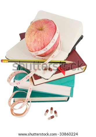 Big ripe apple with measure tape and pills on pile of books as metaphor of healthy eating and diet