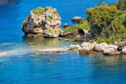 Big rock and narrow path connecting Isola Bella island to mainland Taormina beach surrounded by clear azure waters of Ionian Sea, Sicily, Italy.
