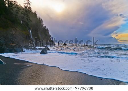 Big rocks and crushing waves against sun rising sky - la push beach forks washington - stock photo