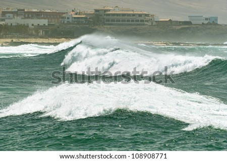 Big roller ocean wave with white foam running along the tropical island beach