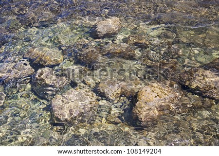 Big round stones under clear sea water.