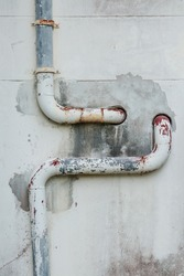 Big rusty pipes on old cement wall