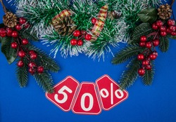 Big sales 50%, fifty percents with Christmas wreath on a dark blue  background, top view, copy space. Christmas big sale.