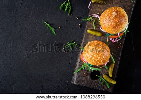 Big sandwich - hamburger burger with beef,  tomato, basil cheese and arugula. Top view. Flat lay
