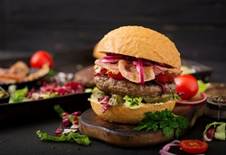 Big sandwich - hamburger burger with beef,  tomato, pickled cucumber and fried bacon