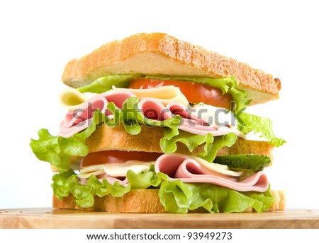 big sandwich with fresh vegetables on wooden board on white background