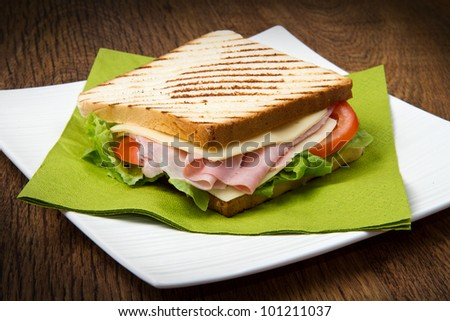 big sandwich with ham, cheese, tomatoes and salad on toasted bread