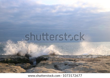 Big sea wave crashing against rocks cause water splashing and spray.