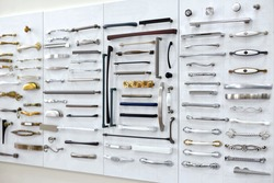 Big selection of handles cabinets parts on a white background shop window. samples of Metal and Stainless Steel handle styles on wooden kitchen cabinet with different Stainless Steel handles.