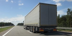 Big semi truck on beautiful asphalted empty highway road in Europe at Sunny summer day, back side view, transportation international logistics cargo insurance