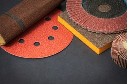 Big set of abrasive tools and multicolored sandpaper on black background, wizard is used for grinding items