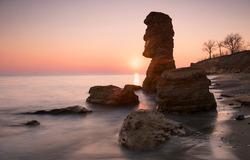Big shell stone like idol, sunrise behind and sunny path to the sea. Long exposure
