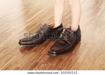 Big shoes to fill, child's feet in large brown shoes, on walnut parquet floor.