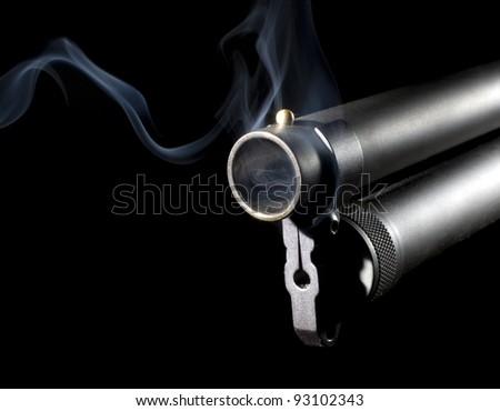 Big shotgun that has blue smoke coming from its barrel