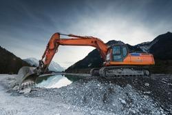 big shovel excavator standing on gravel stones before lake