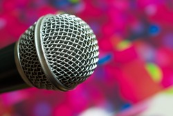 Big silver microphone in concert hall with defocused bokeh lights on background