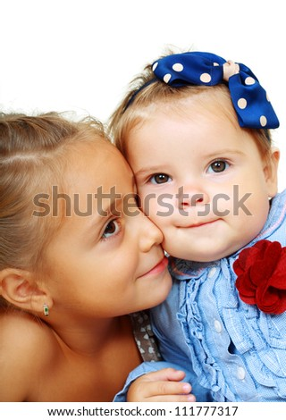 Big sister and little sister kissing on a white background.