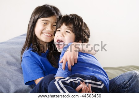 Big sister holding her disabled little brother