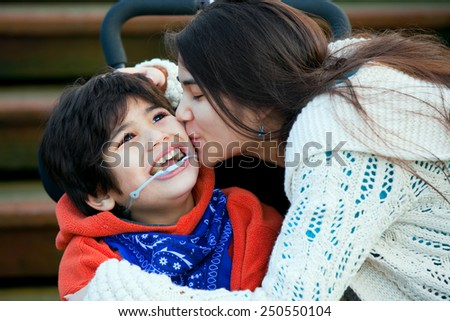 Big sister kissing disabled little brother seated in wheelchair on cheek Stock photo ©