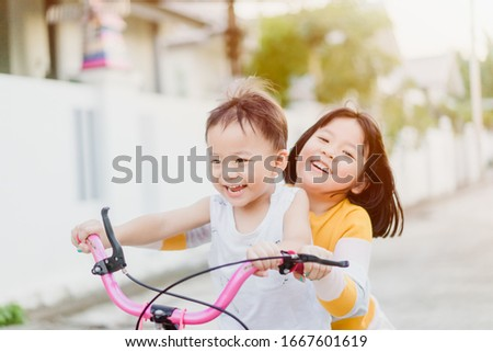 Big sister try to ride bicycle with her brother ride in front on the road in summer.Asian sibling kid playing and ride bike together.Family with children at home.Love, trust and sibling fun together.