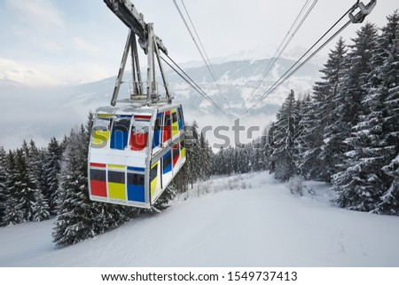 Big ski lift cabin cable car above a valley, connecting two mountains, Vanoise express between Les Arcs and La Plagne of Paradiski #1549737413