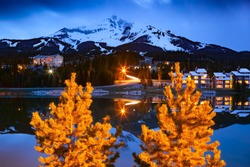 Big Sky Montana, United States, Big Sky Mountain Village ski resort on dusk, dwarfed by the enormity of Lone Mountain full of snow in the Madison Range, Montana USA.
