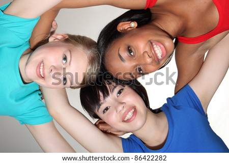 Big smiles in fun team group huddle by mixed race african american, oriental Japanese and blonde caucasian teenage school student girl friends looking down to camera.
