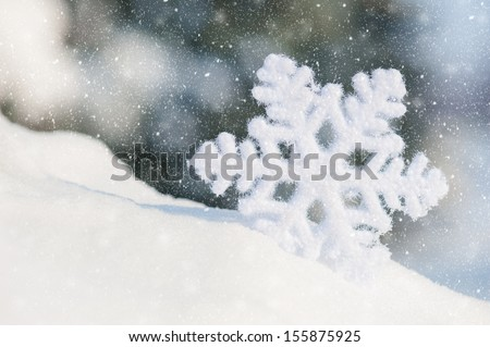 big snowflake toy in snowdrift on hill