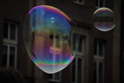 Big Soap Bubble on The Street and Detail of Historical House in The City Center. Dark Background.