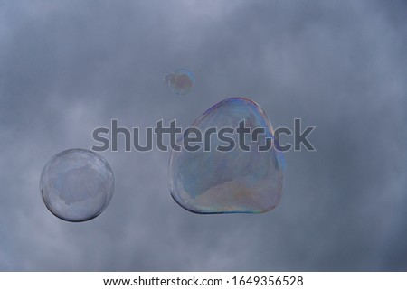 Big soap bubbles against the background of cloudy sky