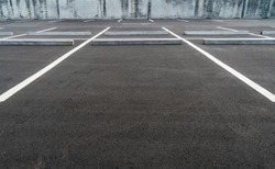Big space at empty asphalt parking lot with concrete car stopper, perspective and low angle view.