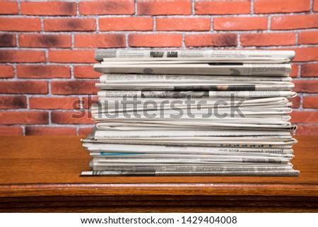 Big stack newspaper of magazines on wooden desk #1429404008