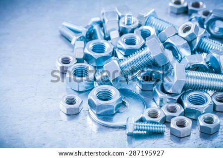 Big stack of metal threaded screwbolts nuts and bolt washers on metallic background construction concept.