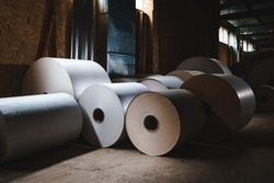 Big Stack of Printing Paper Rolls in Warehouse. The concept of production of paper and paperboard. Industry, copy space.