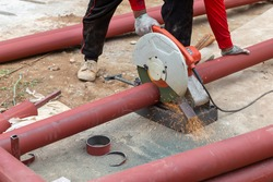 Big steel pipe pipes are being cut from steel cutters by construction workers. Large iron hollow Use it as a roof pole. Sparking occurs while working, the steel pipe is sprayed red to prevent rust