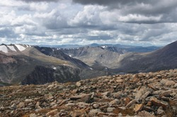 Big stones on the background of valley and high mountain snow peaks ranges under cloudy gloom dark sky Altai mountains Plateau Ukok Siberia Russia