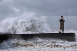 Big stormy sea wave splash over piers and old lighthouse, Portugal