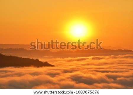 Big sun and mist cover the top of mountain during sunrise with orange white balance. #1009875676