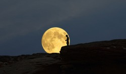 Big super moon and a man on the cliff in the early evening