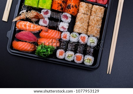 Big sushi set ib black plastic box on black background/ top view close up macro shoot