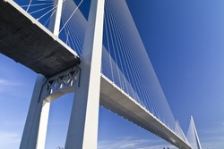Big suspension bridge in beams of the coming sun against the blue sky