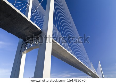 Big suspension bridge in beams of the coming sun against the blue sky #154783070