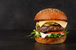 Big tasty burger with beef cutlet on a black stone background