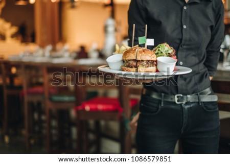 Big tasty burger with fresh salad served by waiter who wear black uniform #1086579851