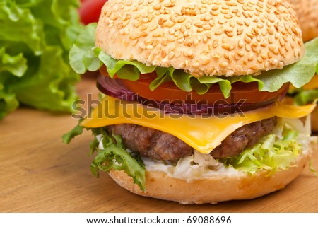 big tasty  cheeseburger on a wooden table