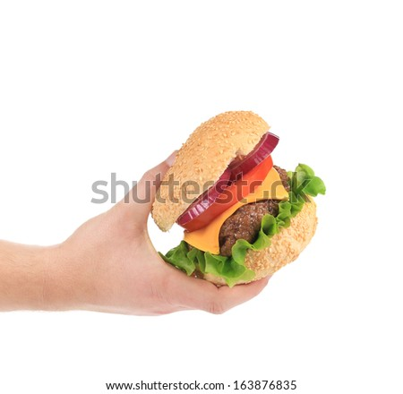 Big tasty hamburger in hand. Isolated on a white background.